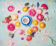 Filiżanka kawy z kolorowymi kwiatami na turkusowego błękita podławym modnym tle, odgórny widok Obrazy Stock