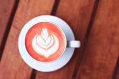 Filiżanka kawy z latte sztuką tonował w koralu obraz royalty free