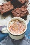 Filiżanka kawy z mlekiem kropi z kakaowym proszkiem i kawałkami czekoladowy tort zdjęcia stock