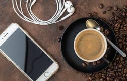 Filiżanka kawy z Mobil i hełmofonami na nieociosanym tle Fotografia Royalty Free