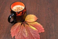 Filiżanka kawy z pianą na brązu drewnianym stole na którym kłama żółtego jesień liść zdjęcie royalty free