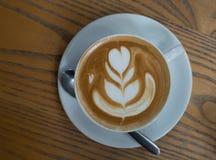 Filiżanka kawy z serce wzorem w białej filiżance na drewnianym plecy Zdjęcie Royalty Free