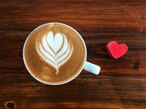 Filiżanka miłość, kierowa latte sztuki kawa w białej filiżance i czerwony miłości serce, Zdjęcia Royalty Free