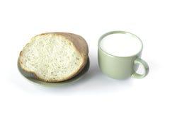 Filiżanka mleko i kawałek odizolowywający na bielu chleb Zdjęcie Royalty Free
