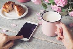 Filiżanka mleko i telefon w rękach Obrazy Stock