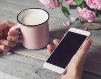 Filiżanka mleko i telefon w rękach Fotografia Royalty Free
