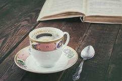 Filiżanka na ciemnym wieśniaka stole z łyżką i książką Drewniany tło Zdjęcia Royalty Free