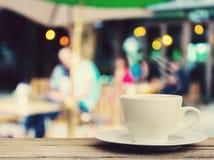 Filiżanka na drewno stole z plamy sklep z kawą tłem Zdjęcie Royalty Free