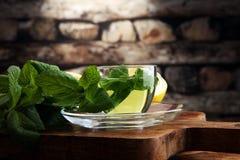 Filiżanka nowa herbata i liście mennica na stole Obraz Stock