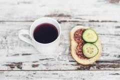 Filiżanka owocowa herbata z kanapką na rocznika drewnianym stole Obrazy Royalty Free