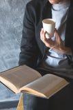 Filiżanka papier kawa, czytelnicza zaciszność fotografia stock