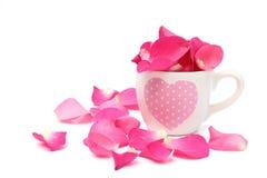 Filiżanka pełno różani płatki na białym tle zdjęcie stock