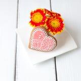 Filiżanka pełno różowi gerbera kwiaty i kierowy kształta ciastko na whi Obraz Stock