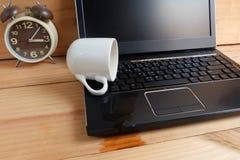 Filiżanka rozlewa out na laptop klawiaturze na drewnianej podłoga Zdjęcie Stock