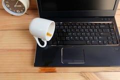 Filiżanka rozlewa out na laptop klawiaturze na drewnianej podłoga Zdjęcia Stock