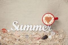 Filiżanka, słowa lato i sieć z skorupami na piasku, Zdjęcie Stock