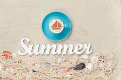 Filiżanka, słowa lato i sieć z skorupami na piasku, Zdjęcia Royalty Free