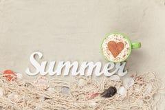 Filiżanka, słowa lato i sieć z skorupami na piasku, Obrazy Stock