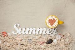 Filiżanka, słowa lato i sieć z skorupami na piasku, Fotografia Stock
