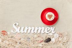 Filiżanka, słowa lato i sieć z skorupami na piasku, Fotografia Royalty Free