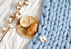 Filiżanka z cappuccino, croissant, błękitna pastelowa gigantyczna szkocka krata zdjęcie royalty free