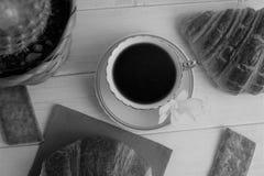 Filiżanka z kawą espresso, croissants, ciastka, kaktus w koszu, orchidea na drewnianym tle, czarny i biały Zdjęcia Royalty Free