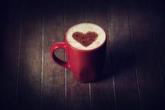 Filiżanka z kawą i kształtem cacao serce na nim. Zdjęcia Royalty Free