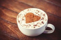 Filiżanka z kawą i kształtem cacao serce na nim. fotografia stock