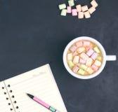 Filiżanka z kawą i marshmallows, puste miejsce otwarty notatnik z piórem na abstrakcjonistycznym czarnym tle na widok Płaski ukła fotografia stock