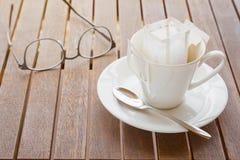Filiżanka z pakującą kawą na lesistym stole, zamazani eyeglas Zdjęcie Stock