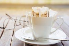Filiżanka z pakującą kawą na lesistym stole, zamazani eyeglas Obraz Royalty Free