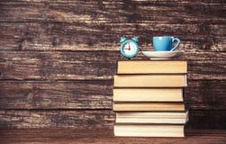 Filiżanka, zegar i książki, obraz royalty free