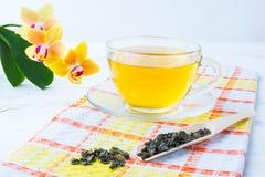 Filiżanka zielona herbata na pomarańczowej w kratkę pielusze Obraz Stock