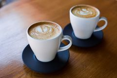 Filiżanki cappuccino z latte dalej wodden stół obraz royalty free