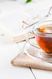 Filiżanki herbata z książką na drewnianym stole Obraz Stock