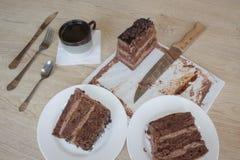 Filiżanki i czekoladowego torta onon drewniany stół Zdjęcia Stock