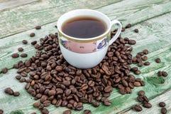 Filiżanki kawa z fasolami na zielonym wieśniaka stole Drewniana tekstura Zdjęcia Stock