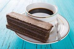 Filiżanki kawy i czekolady opłatki na błękitnym tle zdjęcie royalty free