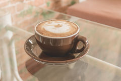 Filiżanki kawy latte na stole w sklep z kawą, rocznika filtra skutek Zdjęcia Stock