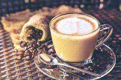 Filiżanki latte cappuccino z sercowatym robić od mleka na drewnianym stole z piec kawowe fasole i sztuka Napój i bre zdjęcie royalty free