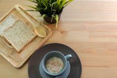 Filiżanki polewka z chlebowym śniadaniem na drewnianym stole Obraz Stock