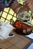 filiżanki ręka nalewa herbacianego teapot Zdjęcia Stock