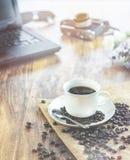 Filiżanki whit kawowa fasola na Drewnianym fotografa biurka stole z ekranową kamerą, laptop obrazy royalty free
