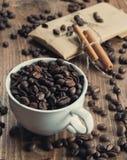 Filiżanek kawy fasole z cynamonowymi kijami i papierowym prezentem Obraz Royalty Free