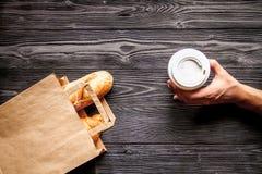 Filiżanka chleb w papierowej torbie na drewnianym tle i kawa Fotografia Stock