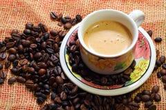 Filiżanka coffe latte pozycja na kawowych fasolach Obrazy Stock