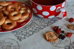 Filiżanka czarna herbata z spodeczkiem, bagels i wysuszone owoc na stole z tablecloth Tradycyjny Rosyjski deser Domowej roboty ba Obrazy Royalty Free
