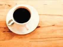 Filiżanka czarna kawa na drewno stole Obrazy Stock