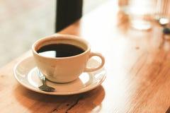 Filiżanka czarna kawa na drewno stole Obraz Stock
