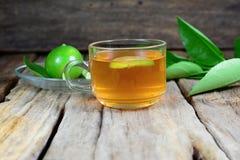 filiżanka herbata, cytryny owoc i zieleni cytryna, opuszcza nad starym drewnem Zdjęcia Stock